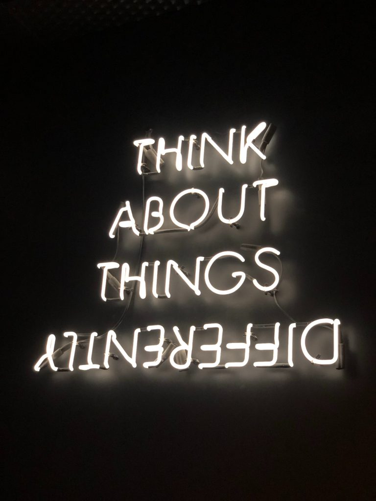 "A neon signed reading ""Think About Things Differently"" with differently spelled backwards."