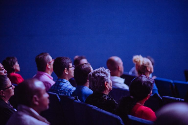 People seated in an auditorium looking spellbound by a presentation.