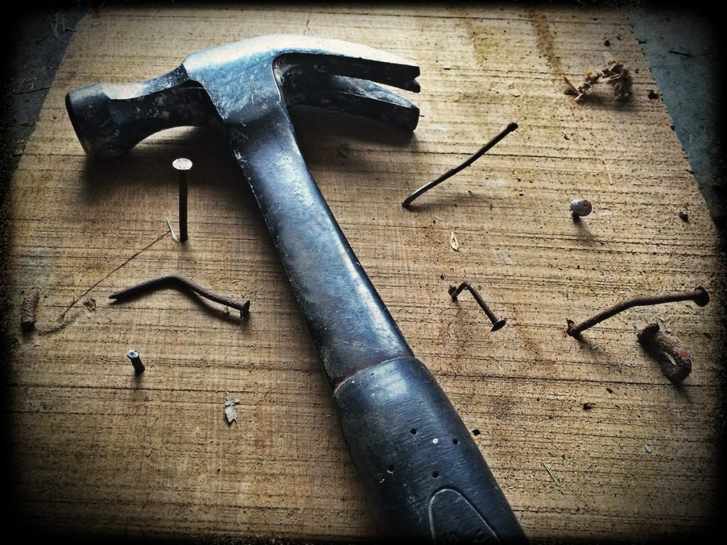 A hammer and numerous bent nails representing doing something challenging