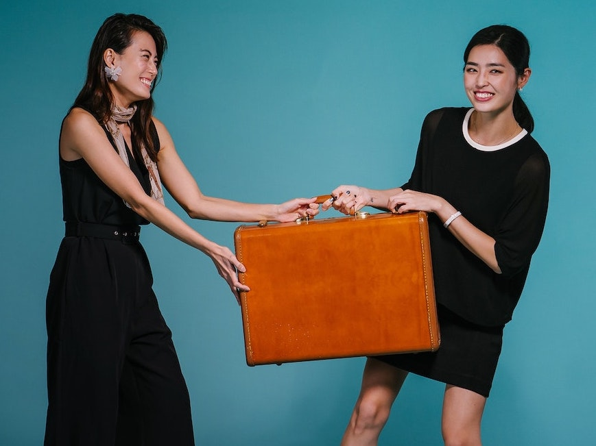 Two women fighting over a briefcase, representing getting help from other businesses.